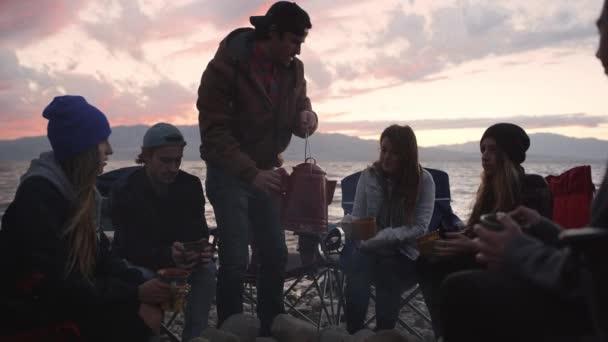 Skupina teenagerů odpočívajících blízko hořícího ohně venku
