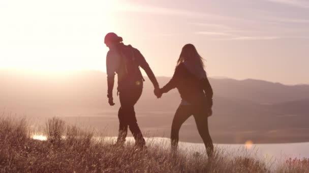Mladý pár v lásce odpočívá v horách při krásném západu slunce