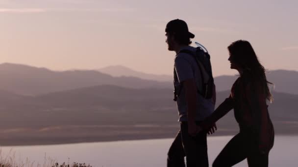 Young couple in love is walking in mountains at beautiful sunset