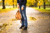 Šťastná žena chůzi v dešti v krásném podzimním parku