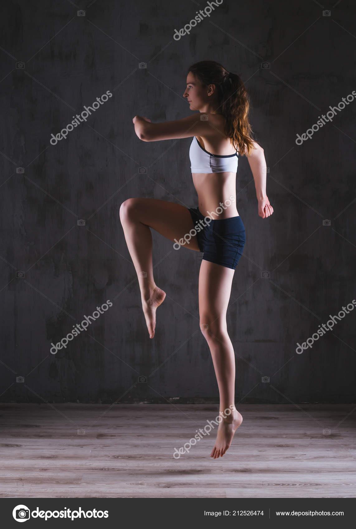 Ausbildung in dunklen Studio Fitness Frau. Junges Mädchen