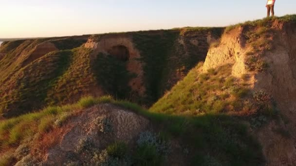 Aerial of a young man standing on a mountaneous hill of the Black Sea at sunset                             An impressive down up pan of a stylish man in sunglasses standing on a green hill with deep gorges nearby at the Black Sea beach at sunset
