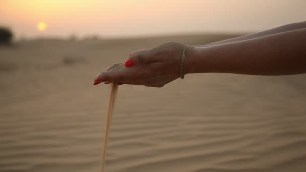 Beautiful female hands keep and sift sand on seashore dunes at a golden sunset                          An amazing view of nice woman`s hands with red makeup keeping a handful of desert sand and permitting it to fall in Dubai at a shimmering sunset