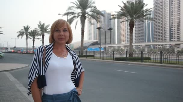 Stylish female tourist standing and smiling at highway with palms in Dubai                                          A cheerful view of an elegant woman standing and smiling happily at a modern highway with palms in Dubai on a sunny day in summer
