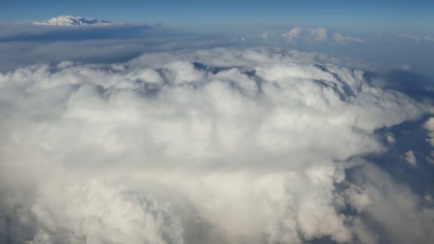 Vzdušný záběr bílých mraků vypadá jako hromady sněhu za slunného dne v létě umělecký pohled z okna letadla z bílou přikrývkou načechraný mraky, šumivé víno bílé, modré a šedé barvy na slunečný den v létě