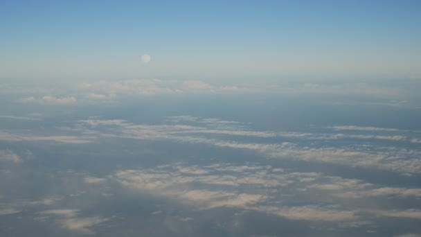 Aerial shot of white cloud lines placed in diagonal way over the land in summer                         A striking bird`s eye view of the stripes of white clouds located askew over the soil from a plane window on a sunny day with blue sky in summer