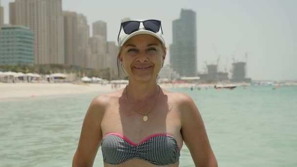 Cheery woman in bikini stands on a sea beach in Dubai and smiles in summer                     Portrait of a cheerful and stylish woman in a white cap and sunglasses on it, and bikini standing on a sandy beach and smiling happily in Dubai in summer