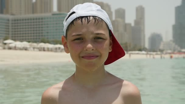Cheery boy in a cap stands in sea water and smiles in Dubai in slow motion                                 Portrait of a small boy standing in sea water in a baseball cap and looking happily with Dubai skyscrapers in the background in slow motion