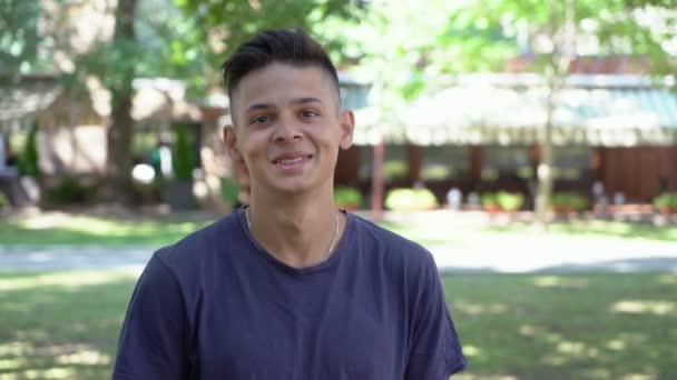 Sportive mladý muž stál a usmíval se v uličce zelený park za slunečného dne portrét sportovní mladíka s účesem posádky a tmavé tričko stojí a šťastně se usmívala v zelený park s loukami a stromy v létě