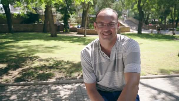 Cheery man sitting on a bench and smiling happily in a green park in summer                            Portrait of a modern man in eyeglasses from Europe sitting on a bench and smiling enthusiastically in a park alley with green trees and sunny lawns