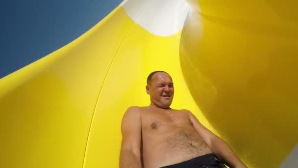 Happy man slides on aqua park tube and keeps a selfie stick in  hand in slo-mo                              An exciting view of a cheery man sliding dowm on yellow tube in aqua park in summer. He smile and shoots with a selfie stick in slow motion.