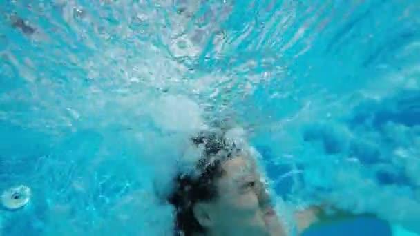 Mladá dívka skáče v bazénu a vypadá legrační pod vodou v pomalém pohybu původní pohled mladé ženy skákání v bazénu a záběr pod vodou. Posílá mnoho bubliny nahoru, vypadá vyděšeně a vtipné v slo-mo