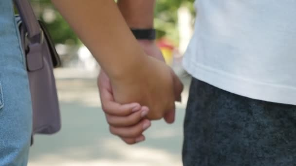 Ženské a mužské ruce držet jeden druhého jako projev lásky v ulici v Detailní zpomalené obě ruce drží navzájem pevně. Patří ke šťastnému páru v lásce chůze po ulici v létě v pomalém pohybu