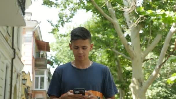 Sportive young man walking along a street surfing the net in summer in slo-mo                            Impressive view of a young brunet man with a short haircut in a black T-shirt going along a green street and browsing the net in slow motion
