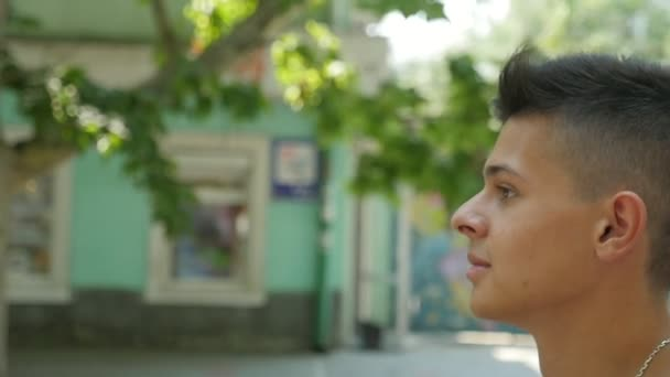 Young brunet man walking along a street with green trees in summer in slo-mo                     Profile of a sportive young man with a short haircut and smart eys going along a street with trees and houses on a sunny day in summer in slow motion