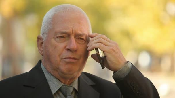 Respektována starý muž v obleku, mluví o telefonu se svým lidem na podzim portrét moudrý senior muže v úhledné obleku s kravatou, lehce se usmál a mluvil s jeho zaměstnanci na smartphone ina ulice na podzim