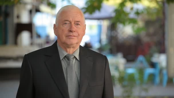 Respectable old man in a business suit puts his hie in order in a street  Portrait of a confident senior man with short haircut in a black  businesssuit putting his necktie in order at a cafe in autumn