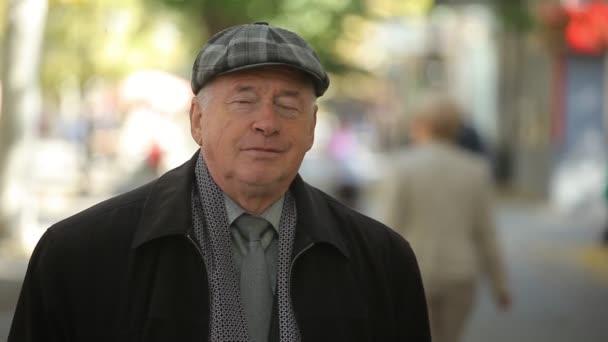 Reliant starší muž v bekovky stojící venku na podzim v zpomalené napínavé portrét veselé muže v kostkované bekovky a vlněném kabátě, stojící v ulici s lidmi na podzim v pomalém pohybu