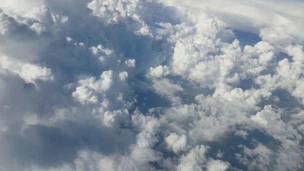Letecký snímek hrubý a kopcovité cloudy z okna letadla v létě vyhlídkou obrovské a načechrané bílé mraky z okna letadla na slunečný den v létě. Obloha mraky vypadají jako shaggy hills.