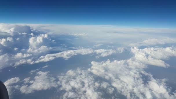 Letecký obrovské nerovnoměrné a hrubé mraky z okna letadla v létě idylický pohled divoký a shaggy bílá oblaka z okna letadla na slunečný den v létě. Zářící nebe celeste je nad.