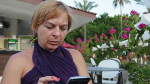 Glamour blond woman sitting and browsing the net on phone outdoors in summer                         Original view of an attractive blond woman in an elegant dress sitting in a cafe outdoors and surfing the net on smartphone scrolling photo in slo-mo