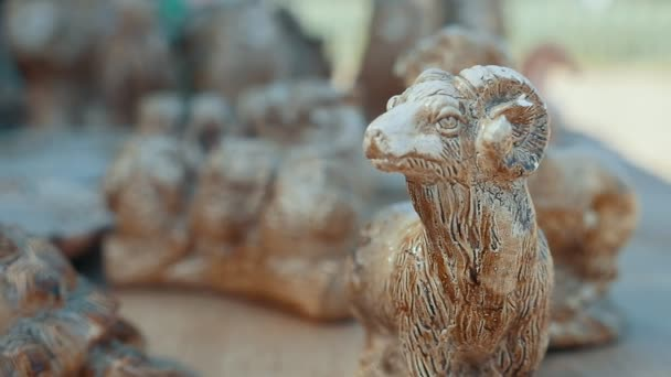 Handmade goat with long horns made of stone among other souvenirs in summer                       Amazing view of a folklore goat with curvy horns placed among other souvenirs showing people and animals made of stone in Askania-Nova in summer