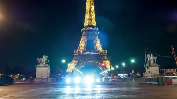 Paris, France - November 3, 2017: Magnificent timelapse of Eiffel Tower illuminated with yellow light, with dashing blue car headlights shining at night in autumn.