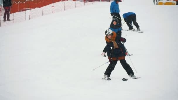 Zakopane, Polen - 10. Dezember 2018: Junge und Mädchen gehen fröhlich gemeinsam Ski und halten die Füße in der Tatra in Zeitlupe breit