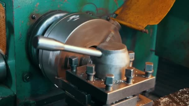 Metallic rod is moving out of a rotating lathe machine on a large workshop                                                                             Professional view of a metallic rod getting out a lathe machine with a handle on large plant