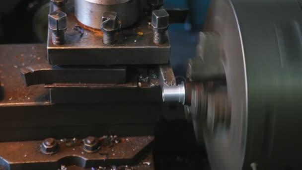 Rotující válec na soustruh stroj řezání kovových žetonů v obrovskou továrnu Detailní záběr velký mosazný váleček loupání kovové žetony na stroje soustruh retro styl