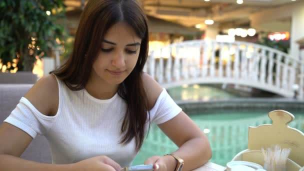 Splendid girl typing sms on her smartpnone in a cafe at a nice fountain                                       Amazing view of a stylish young brunette woman in a fashionable blouse texting a message on her smartphone in a cafeteria near a blue pond
