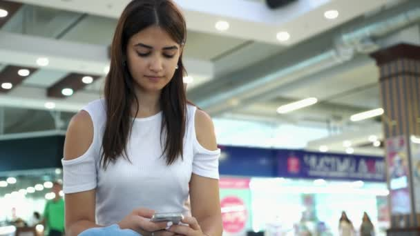 Thoughtful young woman sitting and surfing the internet on her phone in a mall                          Exciting view of a beautiful brunette girl in a stylish white blouse sitting and browsing the net on her smartphone in a large supermarket
