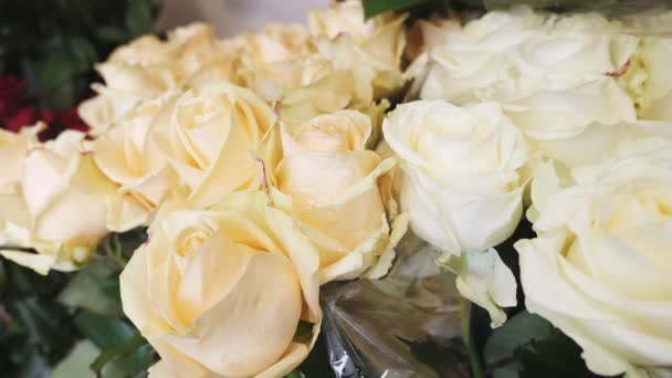 White roses with fragile petals and thorny stems looking fine in a kiosk                                     Stunning closeup view of white roses with tender petals, dainty aroma and thorny stems put in a bucket in a boutique. They look lovely.