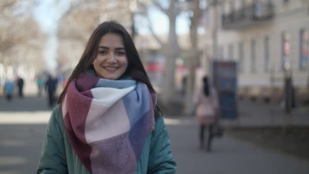 Astonishing view of a beautiful brunette girl with long loose hair and modish scarf smiling and relaxing in a street in winter in slo-mo