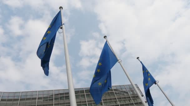 Three EU banners waving at the entrance to the official building in Brussels in spring             Impressive view of three European Union flags fluttering at the EU headquarters in Brussels on a sunny day in spring. The sky is blue and white.