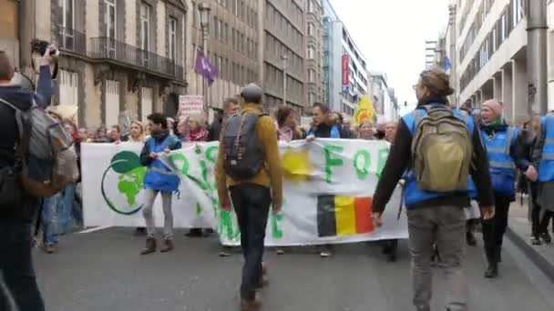 Brussels, Belgium - March 30, 2019:  Impressive view of green-conscious protesters bringing Rising for climate banner and marching for ecology in Brussels on a sunny day in spring