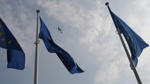 Three EU flag with a police helicopter flying in the sky in spring in slow motion                        Impressive view of the European Union banners flying proudly in the celeste sky with a police chopper soaring high in spring in slo-mo