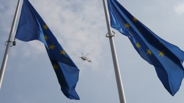 EU banner with a police helicopter on the background. It is symbolic in slo-mo                        Wonderful view of the European Union flag waving in a light blue and cloudy sky with a flying police helicopter in Brussels in slow motion