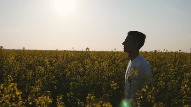 Smiling man in a white T-shirt going in a blossoming field in summer in  slo-mo                              Inspiring profile of a young man in a white T-shirt and black pants going and smiling in a green and yellow field in summer in slo-mo