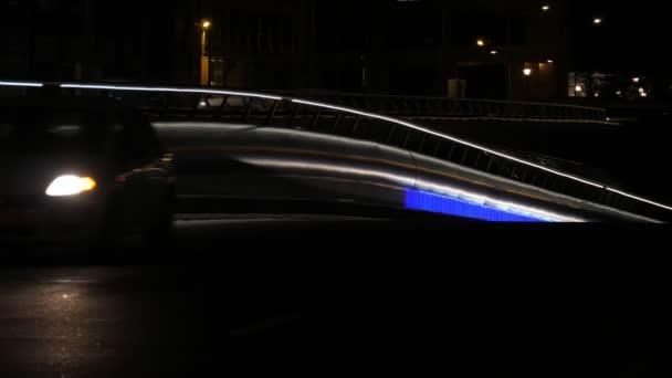 Brüssel, Belgien - 1. April 2019:Wunderbarer Blick auf eine gut beleuchtete moderne Autobahn mit metallischem Straßenzaun und steil geneigter Oberfläche und rauschenden Autos mit geschaltetem Scheinwerfer in der Nacht