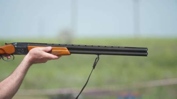 Modern over and under gun popping clay targets on a big range in slo-mo                       Amazing closeup of a  double-barrel shotgun firing at clay targets on a large range on a sunny day in slow motion
