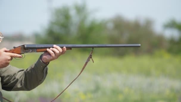 Guy forgatás a side-by-oldalán puska gyakorló Skeet forgatás lassítva pompás Vértes egy okos ember vezetése kettős hordó puska célzás agyag galambok egy napsütéses napon a lassú mozgás