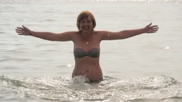 Inspired woman raising hands aside in sea waters in Alanya in slow motion                               Cheerful view of a playing blond woman in bikini raising handfs aside of shining Mediterranean Sea waves in Alanya at nice sunset in slo-mo