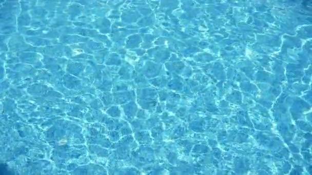 Zářící Indigo vody v plaveckém jezírku v letovisku Alanya v létě v slo-mo inspirativní pohled na třpytivé indiánské vody pokryté pavelou zlatých slunečních paprsků v pěkným bazénu v Alanyi v pomalém pohybu