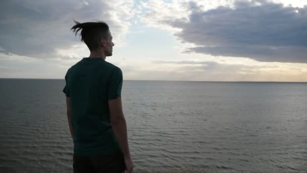 Inspired young guy standing and looking at the Black Sea waters in slo-mo          Emotional back pan of a happy young man with waving hair in a T-shirt and black pants standing and getting inspiration at the Black Sea waters in summer in slo-mo