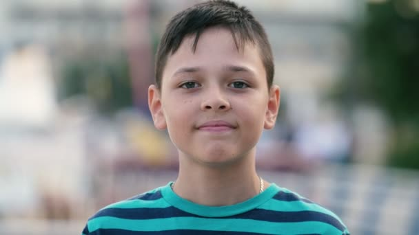 Happy brunet boy standing and smiling cheerily on Dnipro embankment in slo-mo         Optimistic portrait of small brunet boy with crew haircut in striped T-shirt standing and smiling happily on Dnipro embankment on a sunny day in summer in slo-mo