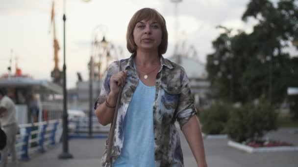 Confident and stylish blonde woman walking on Dnipro quay in summer in slo-mo          Wonderful view of a successful blonde woman with bob haircut in modish colorful shirt, T-shirt, with a leather purse strolling on Dnipro quay in summer in slo-mo