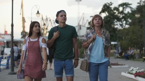 Cheery brunette man and two elegant women walking in a park in summer in slo-mo       Splendid view of an athletic man in a cap, green T-shirt, and shorts, walking with a gorgeous brunette girl and a fashionable blonde woman in a green park in slo-mo