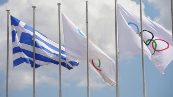Two Olympic and one Greek banners fluttering on flagpoles in summer in slo-mo         Exciting view of one Greek flag and two white Olympic banners waving on high flagpoles in Athens on a sunny day in summer in slo-mo. The sky is celeste and cheery.