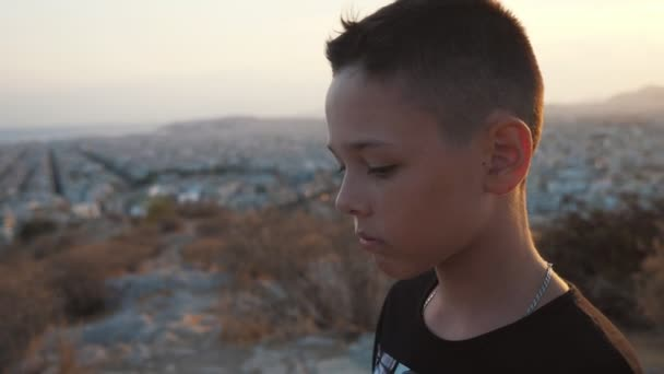 Small boy standing atop of a hill and looking at a city landscape in summer           Impressive view of a small brunet boy with short haircut in a black T-shirt standing atop of a hill and looking at a horizonless cityscape on a sunny day in summer